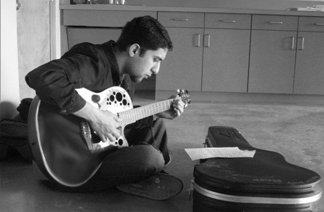 Raef. Black and white photo of man with short dark hair sitting on floor playing guitar in front of guitar case, wearing dark colored shirt and pants.