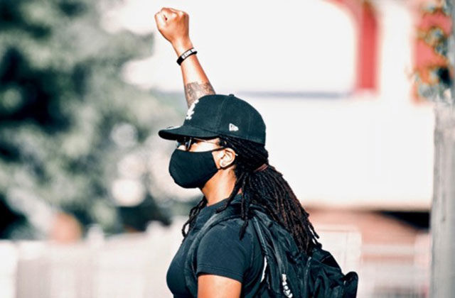 Autostraddle. Black woman wearing black cap, black face mask, black Tee and black back pack with one fist raised in the air.