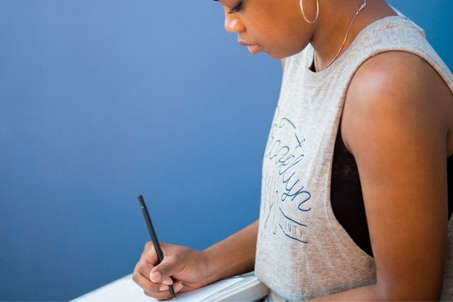 African American woman with pen and pad, writing