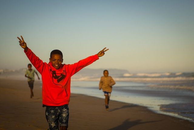 Black Boy Joy. Three black boys running on the beach, the closest, about 9, is smiling from ear to ear.