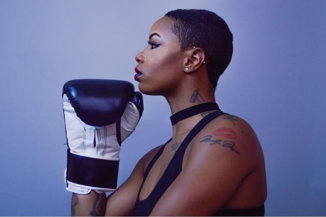 Black woman with tattoos holding her chin like the thinker with a boxing glove