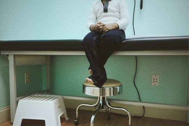 Shot of person waiting in a doctors office. Sitting on a table, with jeans on and barefoot