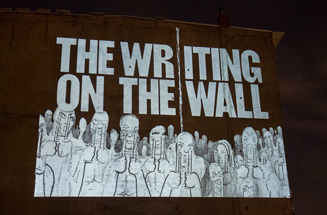 Writing on the Wall. Artwork in white letters read: THE WRITING ON THE WALL, with abstract sketches of people, over a brown wall