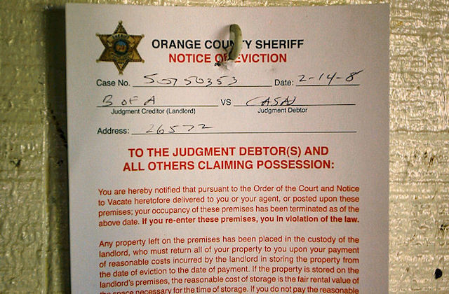 A paper eviction notice from the Orange Country Sheriff hanging on a door.