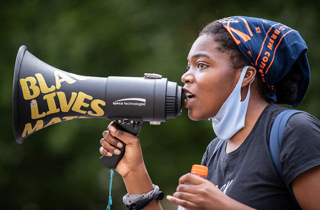 BLM-protest. Young Black woman wearing blue and orange headkerchief, white face mask around her chin and black Tee holding black bullhorn reading Black Lives Matter in yellow words.