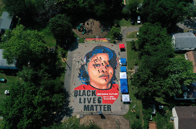 Breonna Taylor mural. Large paining on ground surrounded by trees in a neighborhood of a young Black woman with blue hair and red shirt.