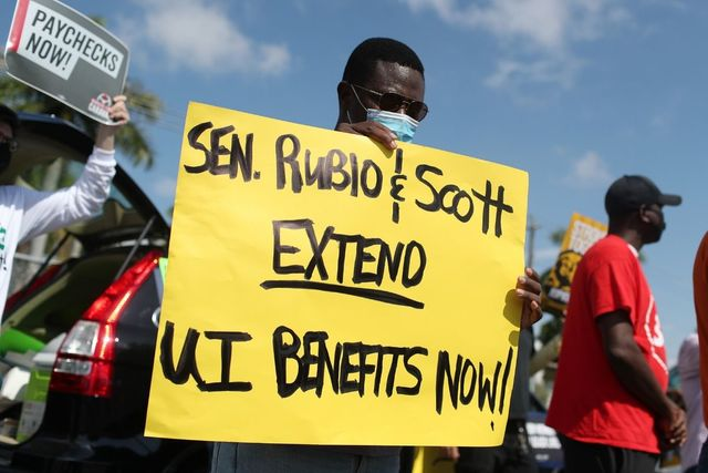 "Protest. Black man with mask on holding a yellow sign saying ""Sen. Rubio & Scott Extend UI Benefits Now!"""