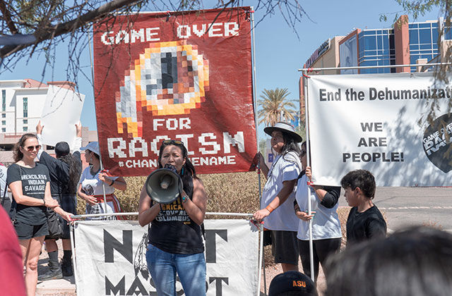 Imagining the Indian. Woman on stage wearing black tee and blue jeans holding a bullhorn in front of a huge banner reading: Game Over for Racism.