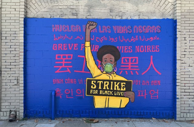 Brian-Herrera's art. Mural showing Black girl with black Afro wearing yellow and raising a fist.