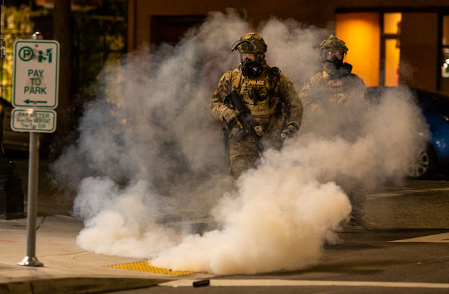A federal officer wearing military gear walks in a city street surrounded by tear gas.