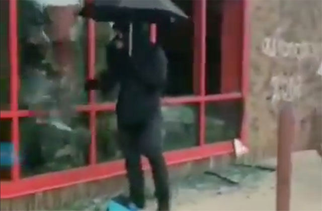 Umbrella Man. Man carrying a black umbrella dressed in all black on the street.