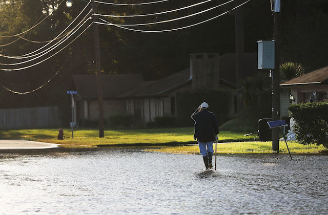 An outdoor shot of a Black man walking through flooded streets towards a house