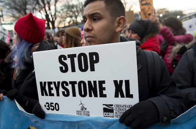 "A shot of a young brown man standing outside at a protest and holding a sign that reads ""Stop Keystone XL."""