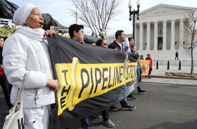 "A line of activists stand in front of Supreme Court holding a banner that reads ""The Pipeline Stops"""