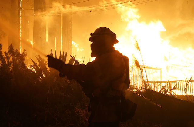 The shadow of a firefighter can be seen in the forefront as a fire rages in the background.
