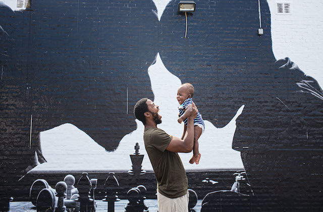 A Black man is holding a baby up in the air in front of a painted mural with a father and son.