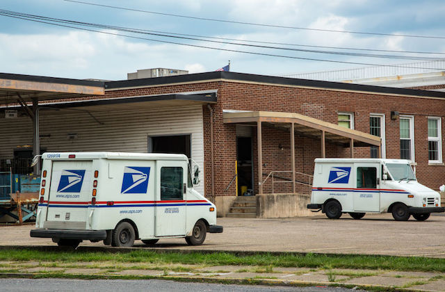 Two mail trucks are parked in an otherwise empty parking lot.