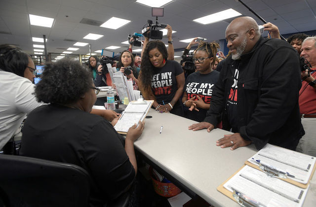 One Black man and two black women stand in front of a desk waiting on paperwork while wearing t-shirts that read, Let My People Vote.