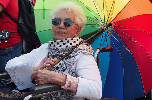 LGBTQ ELDER. Brown elder woman in a wheelchair with short gray hair holding a rainbow colored umbrella.
