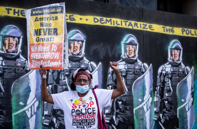 "A  protester wearing a mask holds a raised black power fist holds a sign that reads, ""American was never great! We need to Overthrow this system!"" in front of a mural with NYPD officers in full riot gear and the banner above them that says, ""Demilitarize The Police"""