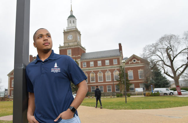 young Black man leans on a poll and looks at the sky as the Howard University campus sits in the background.