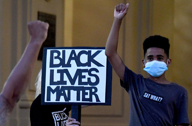 Protest. Young Black boy wearing face mask and blue Tee shirt stands with raised fist in front of sign reading: Black Lives Matter.