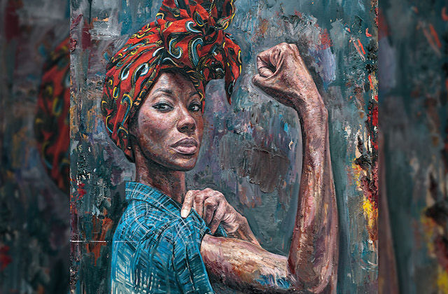 A Black woman with a read and green headwrap and a blue demin shirt is posing in the Rosie the Riveter stance.
