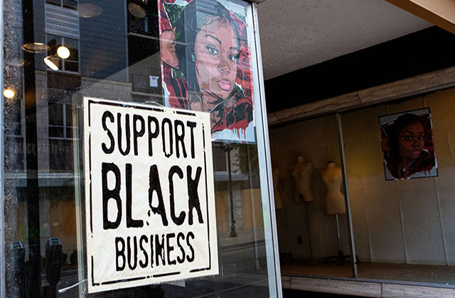Black Business. Sotrefront with a picture of Breonna Taylor on the window and a sign reading Support Black Business.