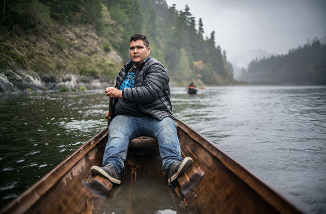 Gather. Indigenous man wearing a black bubble jacket, blue jeans and boots, rowing a boat on a river.