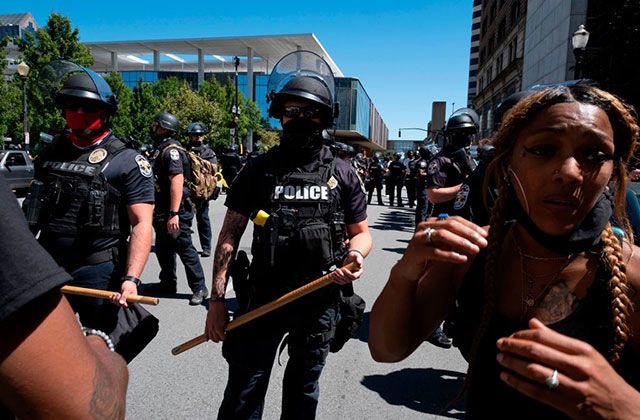 Kentucky-Protests. Black woman with long braids wearing black tank and black face mask moves ahead of a row of police officers holding batons.