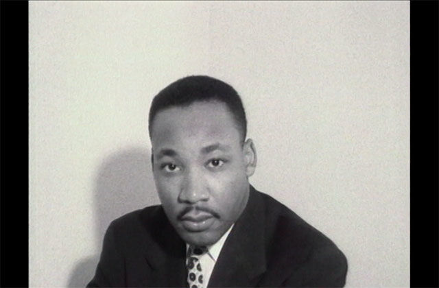 Martin Luther King, Jr. Black and photo of Black man with short dark hair, mustache, wearing a dark suit jacket, white, shirt and tie.