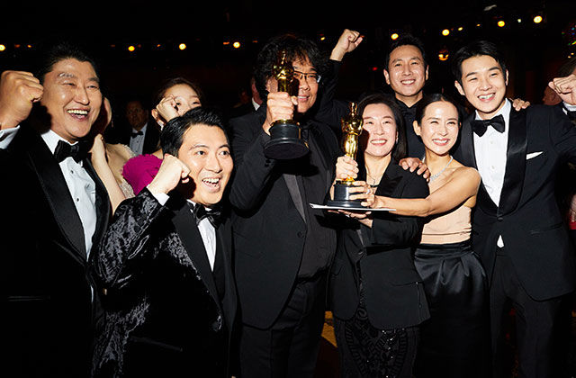 Parasite. Group of Korean men and women dressed in formal black attire holding an Oscar award and cheering.