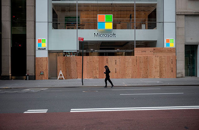 Microsoft. Boarded up storefront with windows logo  and person wearing all black running by.