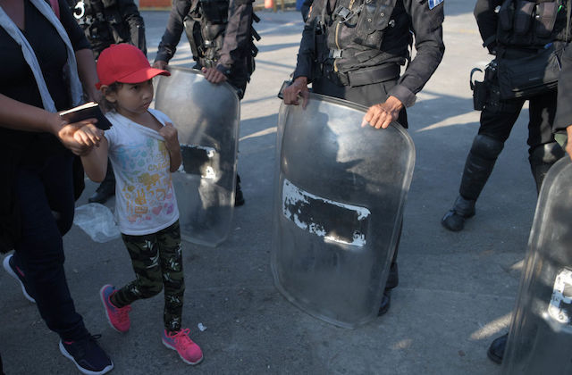 A small girl wearing a red hat hold hands with an adult as they walk past officers wearing riot gear.