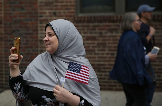 A woman wears a gray hijab smiles as she holds a small American flag and a smartphone.