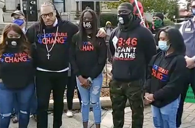 "I-AM-THE-CHANGE-MARCH. Two Black men and three women wearing black shirts reading ""I Am the Change"" stand together."
