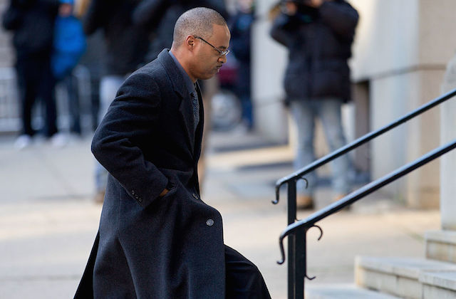 Black man in glasses and a long drak-gray wool coat walks up a set stairs, outdoors