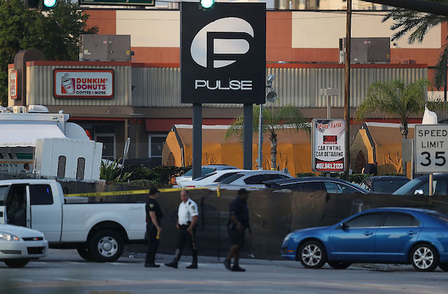 Police officers and vehicles sit in front of a black and white sign for Pulse Orlando