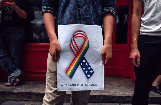 "Man holds sign with rainbow and American flags in joint ribbon, reading ""we stand together with Orlando"""