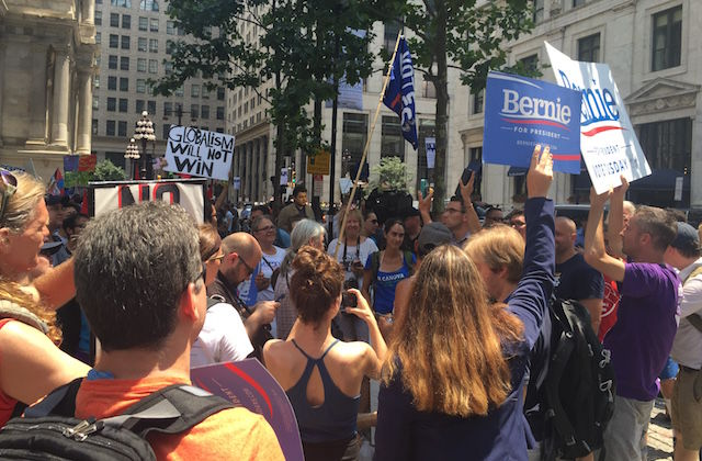 Bernie Sanders supporters holding blue signs with white text
