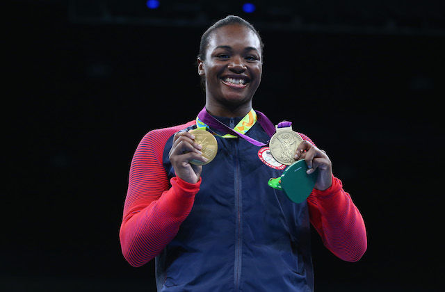 Claressa Shields in navy and red warm-ups, holding two gold medals on green ribbons