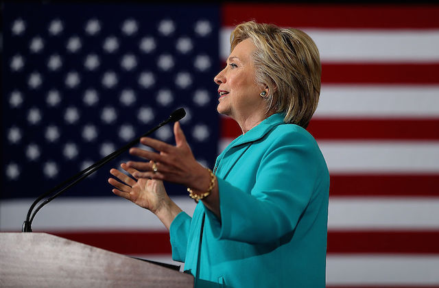 White womanin teal pantsuit speaks at a podium