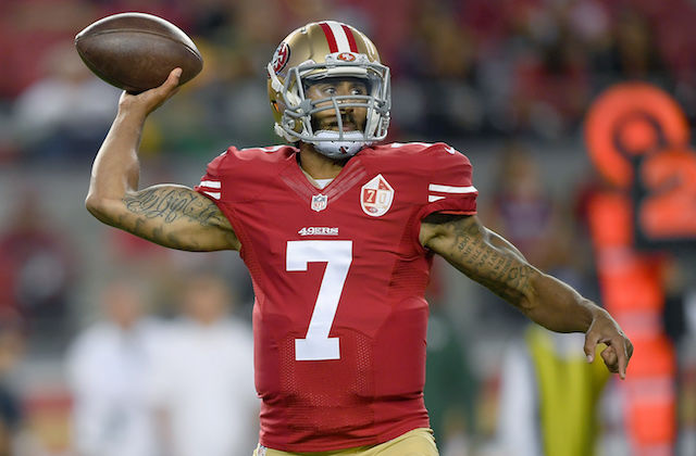 "Colin Kaepernick in red jersey with white ""7"" in the middle, brown helmet and holding brown football"