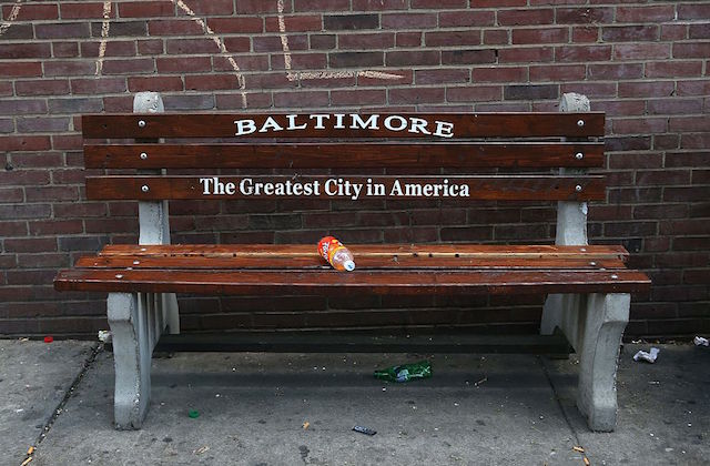 "A brown bench with the following message written on it: ""Baltimore: The Greatest City in America"""