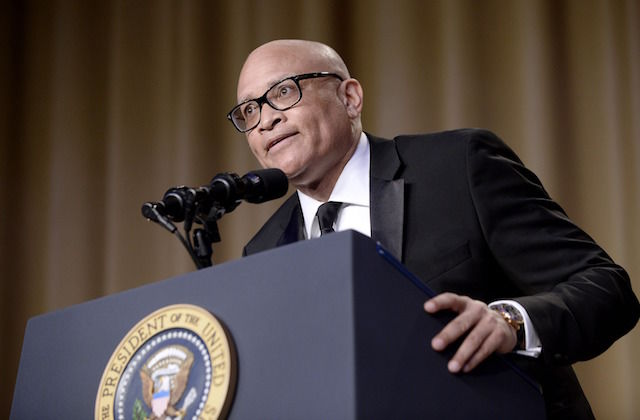 Larry Wilmore in black tuxedo with black tie at navy podium