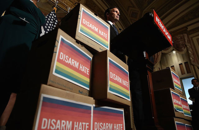 "Man stands at podium flanked by boxes with signs that read ""Disarm Hate"""