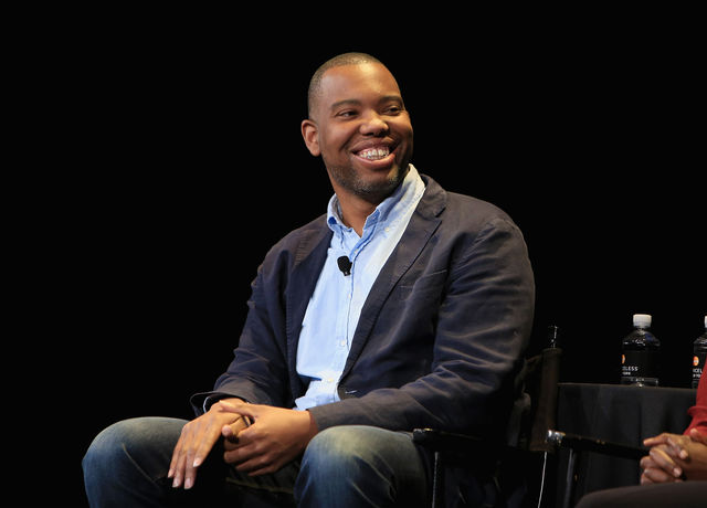 Ta-Nehisi Coates in black jacket with blue collared shirt and dark blue jeans, in front of black background