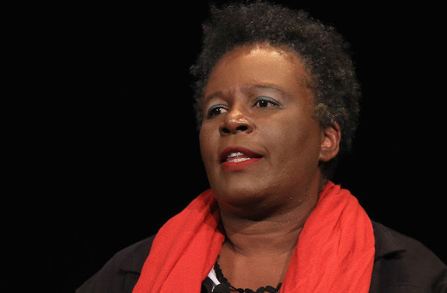Claudia Rankine in black sweater and white shirt with red scarf against black background