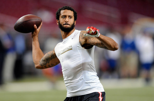 Colin Kaepernick in white warm up shirt holding brown football