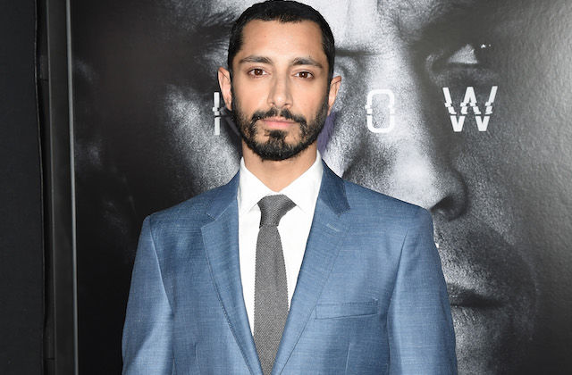 Riz Ahmed in blue suit with white shirt and grey tie against black-and-white background